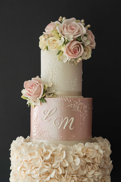 Pretty three-tiered wedding cake in ivory and shimmering pink with ivory ruffles, pale pink roses and delicate lace detail
